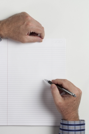 Cropped close-up of human hand writing on book. Stock Photo - 17189458