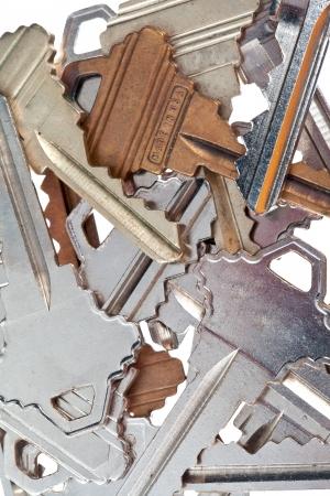 Detailed shot of old fashioned metallic keys on plain white background.