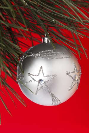 cele: Close-up shot of star shape on Christmas bauble hanging on Christmas tree against plain red background.