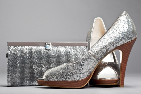 Glittering high heel shoes with a matching purse displayed on grey background.