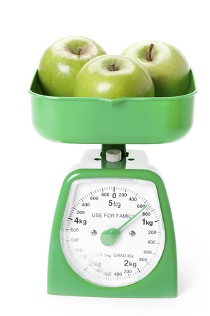 heaviness: Green apples weight measured by a green weighing scale.