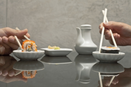 Human hands holding sushi with chopsticks at restaurant