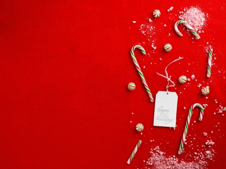Close-up shot of happy holidays tag with damaged candy canes on plain red background. Stock Photo - 17210153