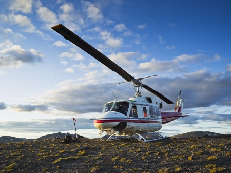 A helicopter parked on a mountain side