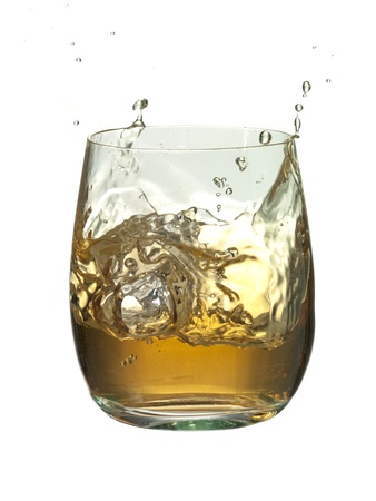 Close-up image of an ice cube splashed into the glass of brandy against the white background Imagens