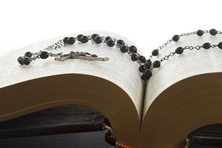 detailed shot: Detailed shot of a rosary bead with holy bible displayed on white background. Stock Photo