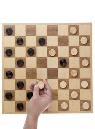 checker board: La mano del hombre la celebraci�n de corrector ortogr�fico pieza sobre placa contra el fondo blanco Foto de archivo