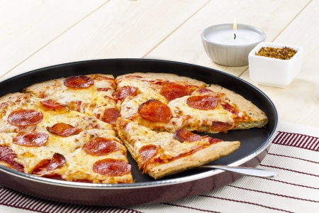 lighted: A pan of pepperoni pizza with serving spoon on a wooden table with lighted candle