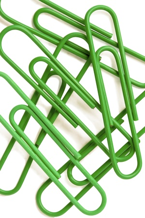 Vertical image of a pile of green paper clip over the white background Archivio Fotografico