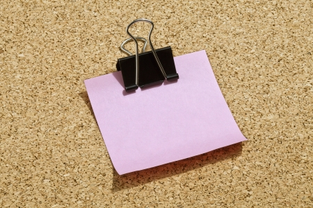 Image of pink post it paper with black paper clip photo