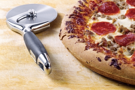 pizza cutter: Pizza cutter and pizza on a brown background
