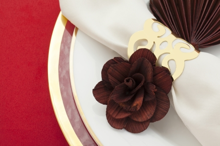 buffet table: Close-up cropped image of plate with a flower design white ring napkin on a red background Stock Photo