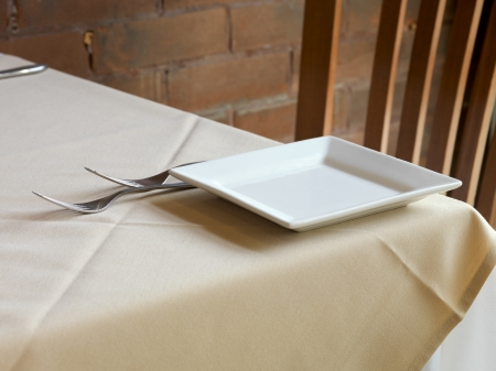 Restaurant table ready with empty plate and spoon on tablecloth. photo