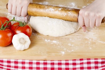 Image of a hand holding a rolling pin to knead the pizza dough on the wooden table photo
