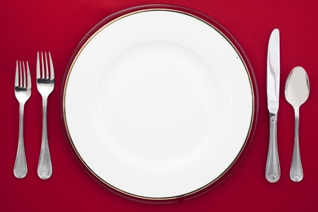 banqueting: Image of a white round plate with knife, spoon and fork over the dinner table Stock Photo