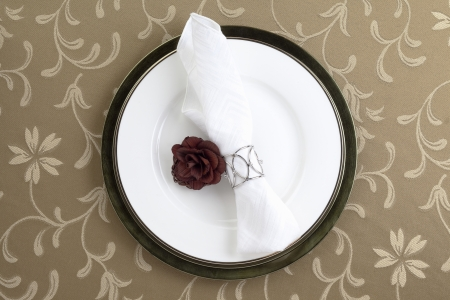napkin ring: A horizontal top view image of plate with a white ring napkin on brown background
