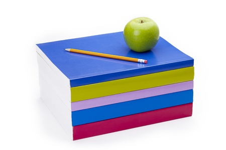 Colourful books with a pencil and apple on top.
