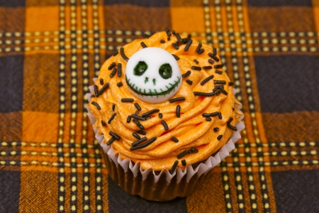 Top view of a cupcake with a skull design displayed on a table cloth. Stock Photo