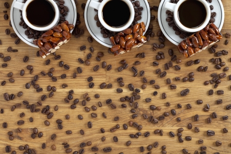 Overhead view of coffee cups with coffee beans and almond confection. photo