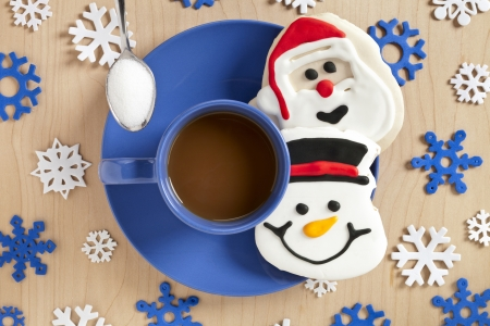 Close-up top view of a blue coffee cup Christmas candies and snowflake design on wooden plank.