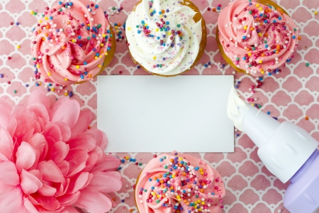 Close-up top view of strawberry cupcakes with empty placard and flower. Imagens