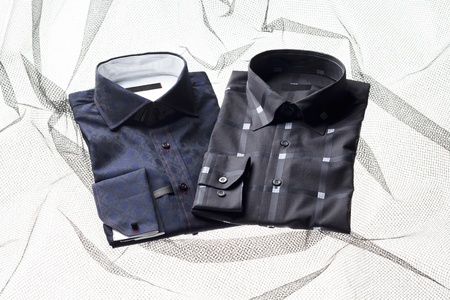 A horizontal image of black and blue shirts with collar over a white printed background photo
