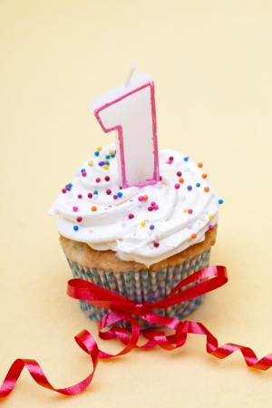 Close-up view of a cupcake with number 1 candle and red streamer around cupcake.