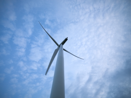 environmental conversation: Low angle view of a wind turbine with sky in the background. Stock Photo
