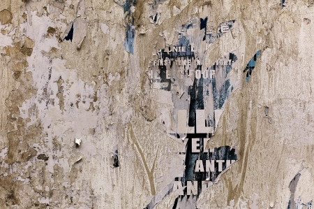 Detailed shot of peeled poster on messy wall. photo