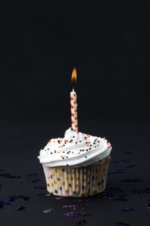 Image of a yummy cupcake with candle on dark background