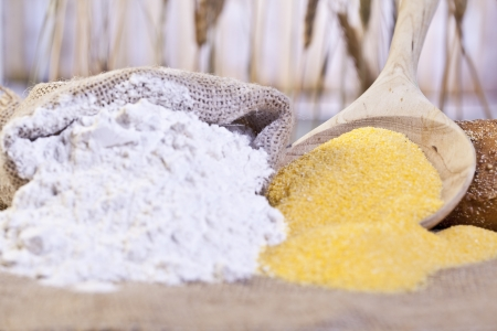 maize flour: Close-up image of sack of flour and maize flour on a wooden table