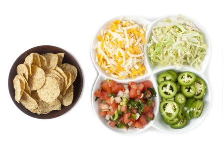 serape: Bowl of nacho chips and a set of different toppings