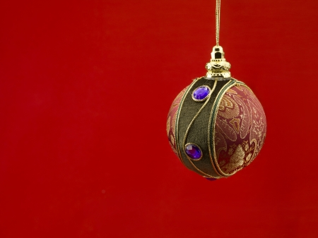 Close-up shot of Christmas bauble against red background. photo