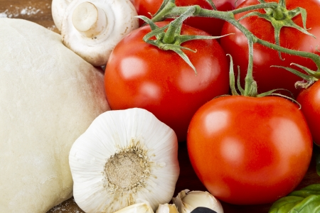 particularly: A close-up shot of different pizza ingredients, particularly on garlic and tomato