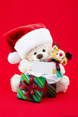 Fluffy christmas teddy bear with gift box and placard over red background. Stock Photo - 17227203