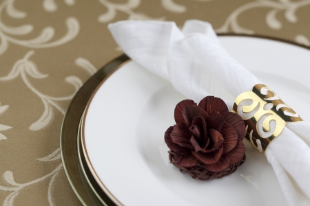napkin ring: Gold napkin ring and flower decoration in a seamless background Stock Photo