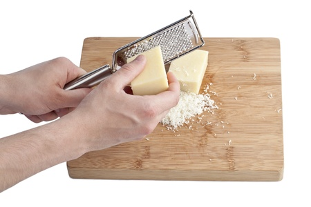 Close up image of human hand grater and parmesan cheese in wooden plate against white background Stock Photo - 17226582
