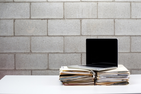 Silver laptop sitting on files with a brick wall as a background. Stock Photo - 17230566