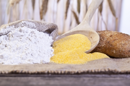 maize flour: Image of bread ingredients with maize flour and a sack of wheat flour on table