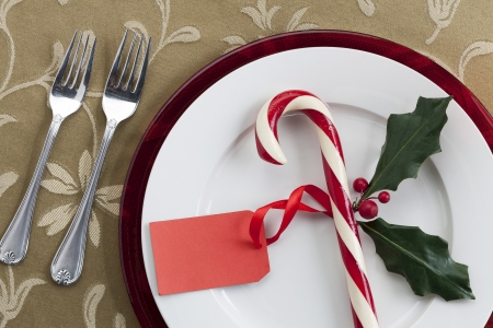 Close-up shot of a dining table with plate, candy cane, blank tag and forks.