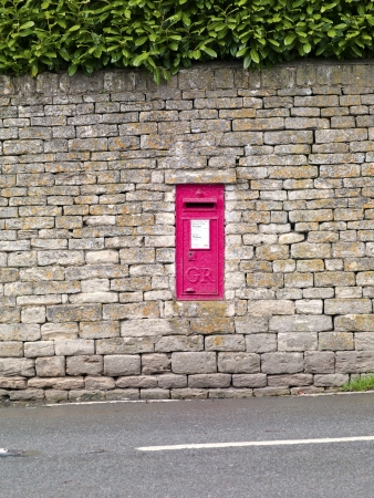 A red postbox in a stone wall in England Stock Photo - 17230681