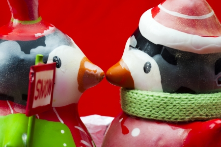 human likeness: Side view of two penguins with placard face to face against red background.