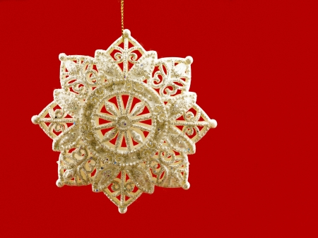Close-up view of golden Christmas bauble against red background. photo