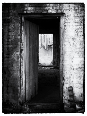 run down: Black and white image of open door of an old structure.