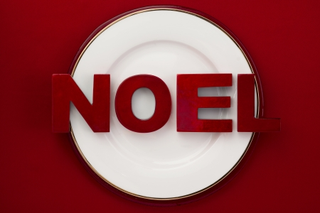 Image of white plate with word noel red background photo