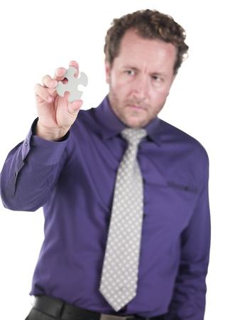 Doctor holding a puzzle piece against white background, Model: Derek Gerhardt Stock Photo - 17256983