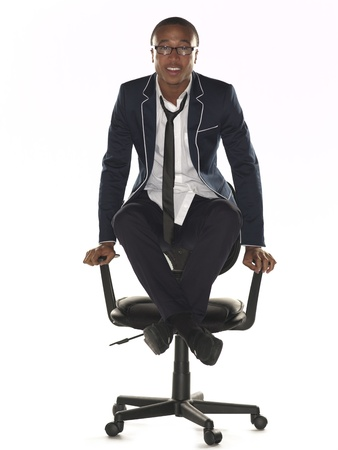 only one teenage boy: Businessman balancing on office chair with legs crossed at ankles over white background. Model: Nathaniel Stevenson Stock Photo