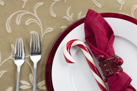 Table napkin and candy cane on a plate with two forks on the side Stock Photo