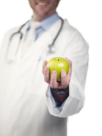 Mid section of a doctor holding green apple against white background, Model: Derek Gerhardt Stock Photo - 17243877