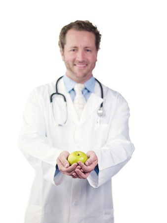 Happy young doctor holding green apple over white background, Model: Derek Gerhardt Stock Photo - 17244420